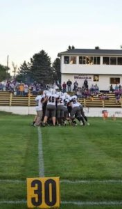The Broncos huddle before the first district game against the Wausa Vikings